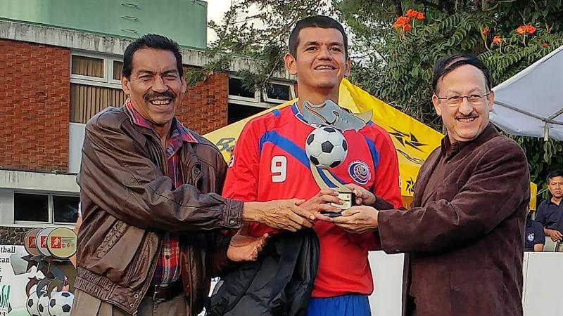 a blind footballer with his trophy