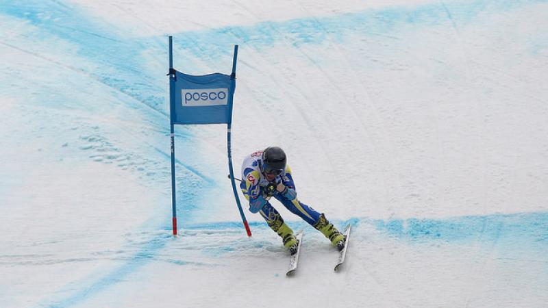 Alpine skier skies down a hill