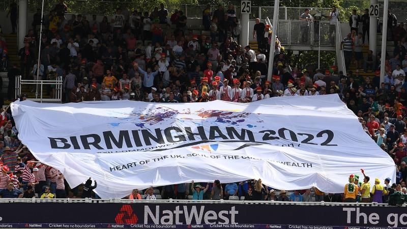 a huge flag is held up by a crowd of cricket supporters