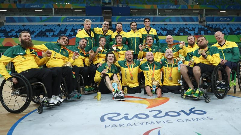 a group of wheelchair rugby players pose on the court with their medals