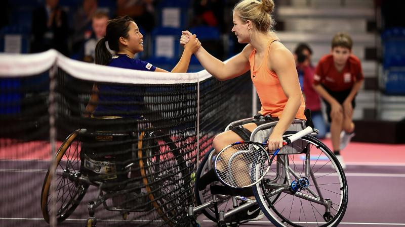 two female wheelchair tennis players shake hands over the net