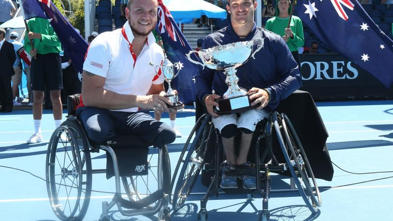two male wheelchair tennis players hold up their trophies