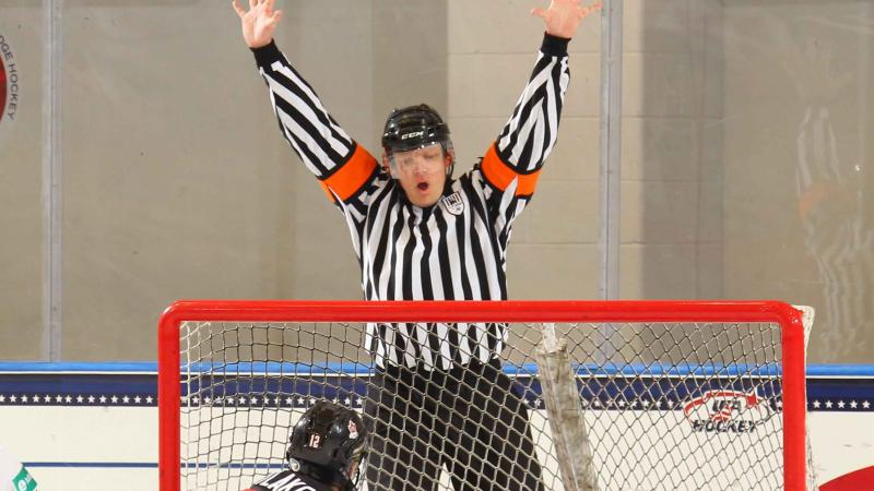a male Para ice hockey referee throws his hands up to signal