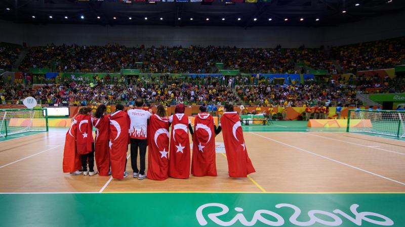a group of women hug under the Turkish flag
