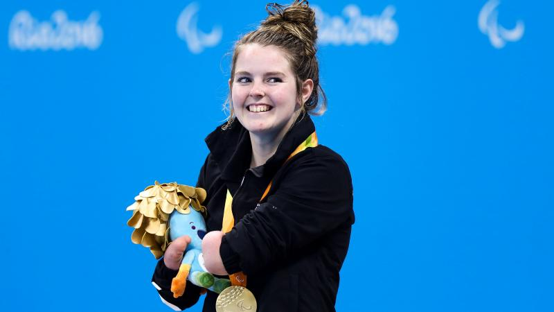 a Para swimmer smiles with her gold medal on the podium