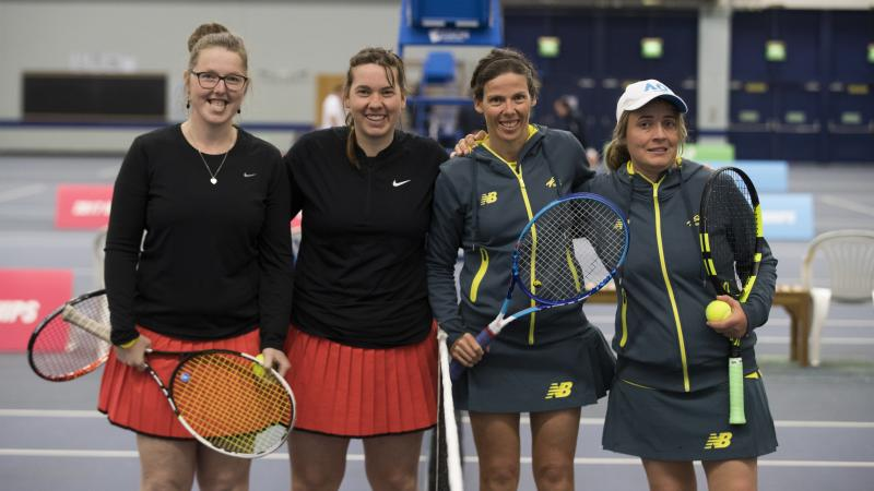 four female tennis players stand at the net