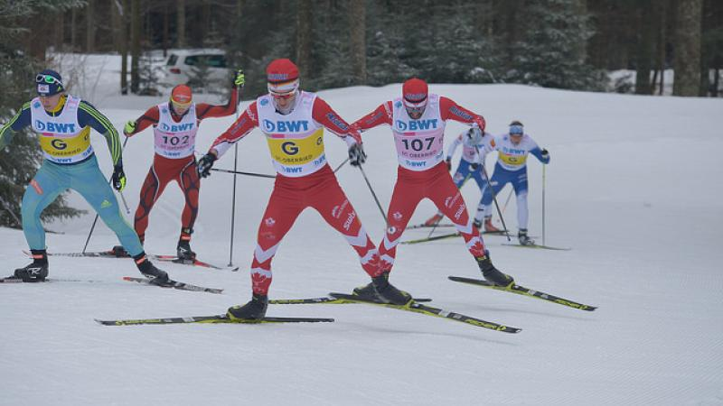 Two vision impaired cross-country skiers race with their guides