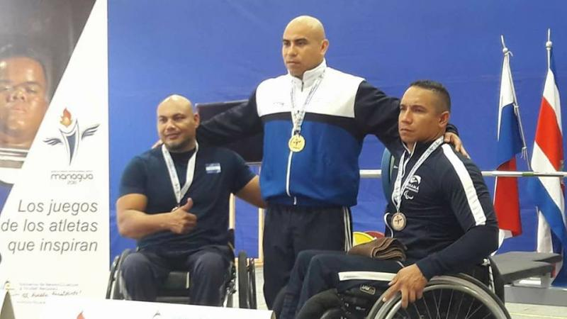three male powerlifters ona podium