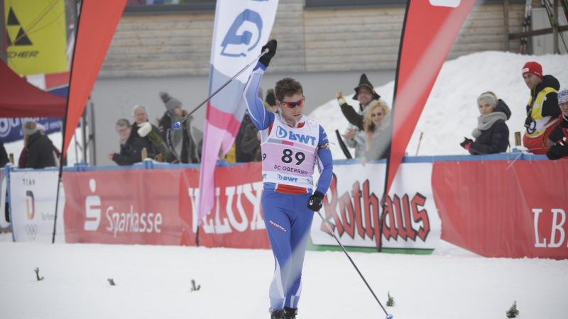 a male Para Nordic skier raises his arms in celebration as he crosses the finish line