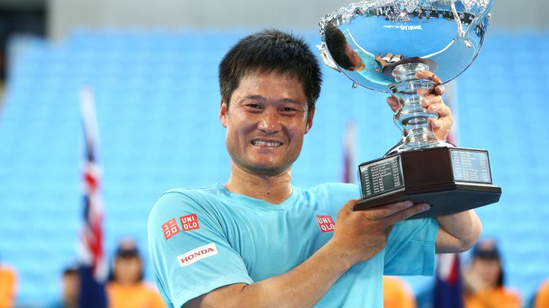 Man smiling and lifting a silver trophy