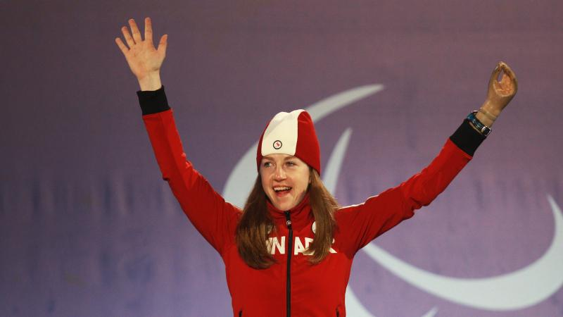 a female Para skier raises her arms in celebration on the podium