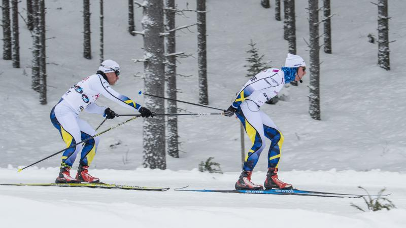 a male Nordic skier and his guide mid-race