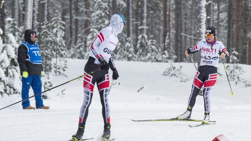 a female vision impaired skier and her guide