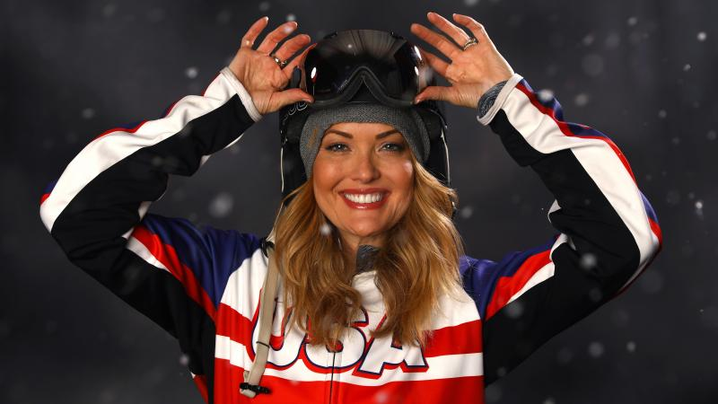 a female Para snowboarder lifts her goggles up onto her head