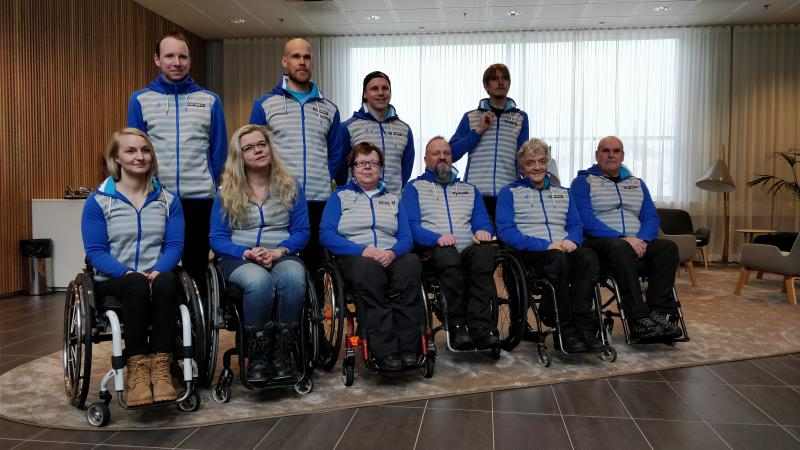 Four people standing behind a group of six people in wheelchairs