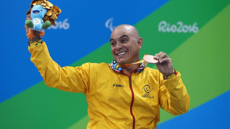 a male Para swimmer holds his bronze medal aloft