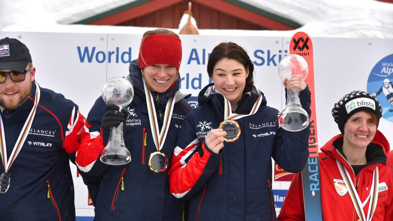 a female vision impaired skier and her guide on the podium