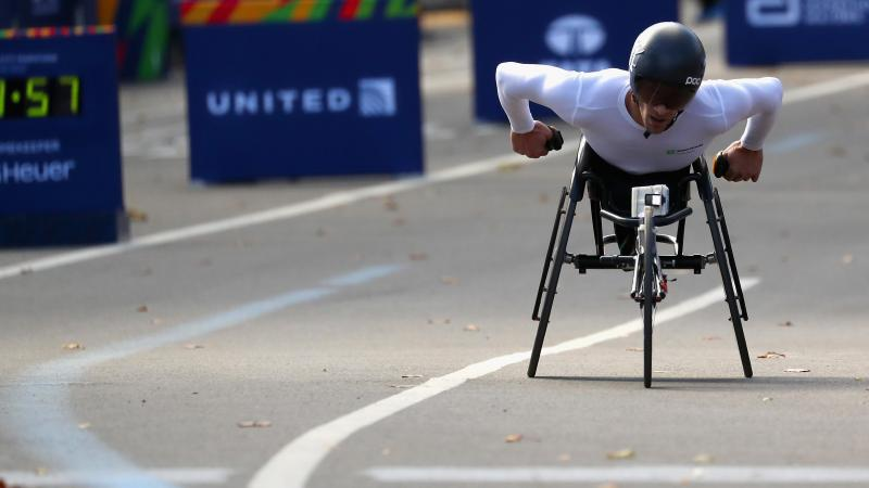 a male wheelchair racer heads towards the finish line