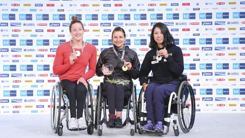 three female wheelchair racers on the podium with their medals
