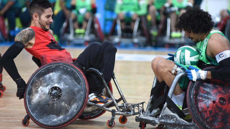 two male wheelchair rugby players clash for the ball
