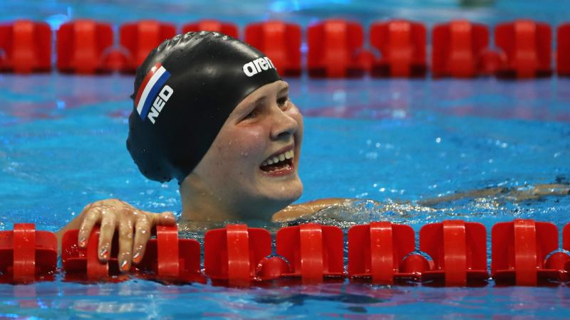 a female Para swimmer smiles in the pool