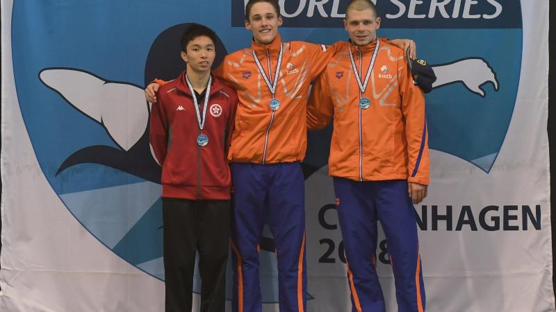 three male swimmers link arms on the podium