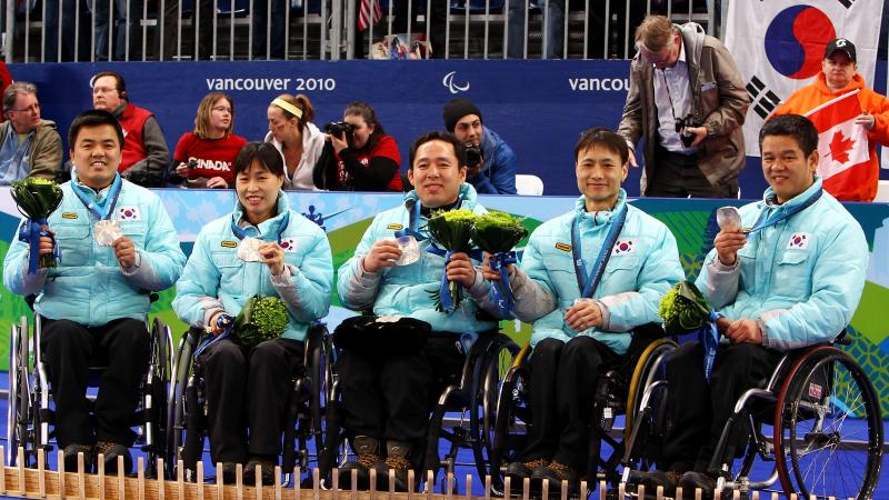 a group of wheelchair curlers celebrate on the podium