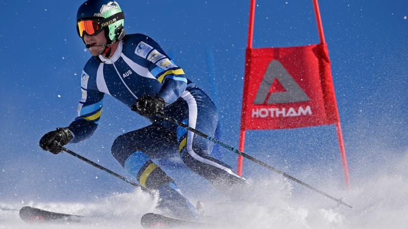 a male vision impaired skier rounds a gate