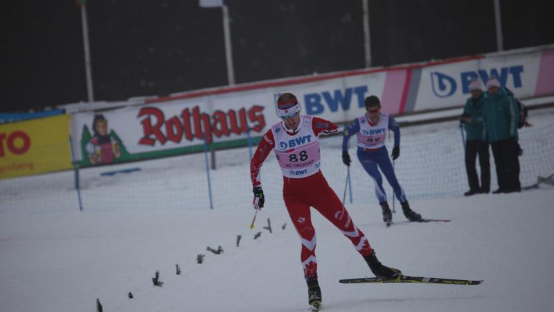 a male biathlete skies towards the finish line