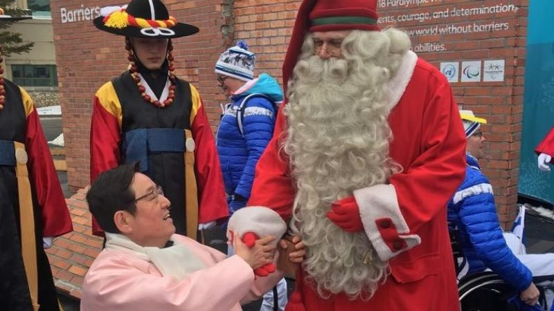 Santa Claus shaking hands with a wheelchair athlete