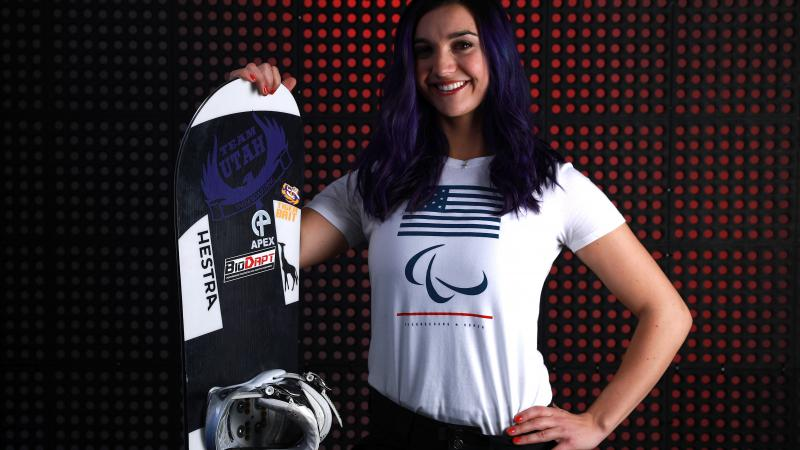 a female Para snowboarder poses with her board