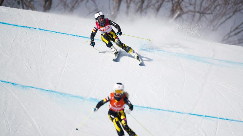 a female vision impaired skier and her guide head down the slope