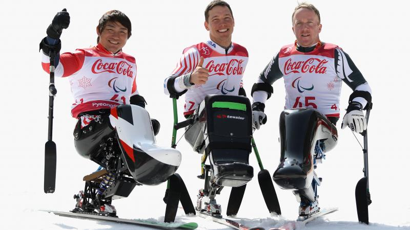 three male sit skiers celebrating on the snow