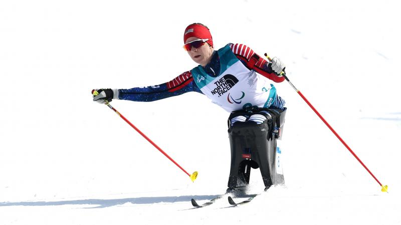 a female sit skier pushes through on the biathlon course