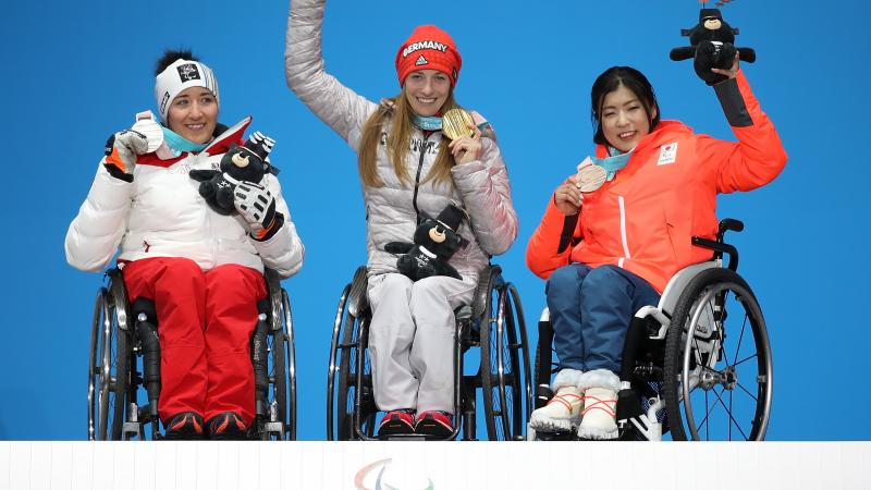 three female sit skiers on the podium with their medals