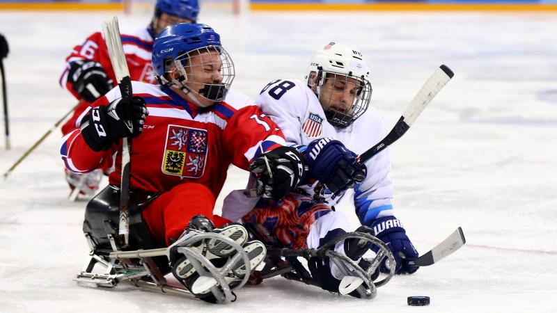 two Para ice hockey players clash on the ice