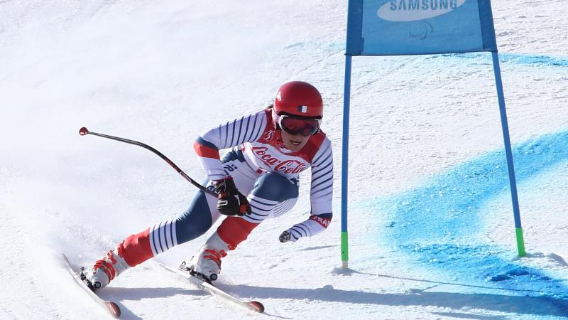 a female Para skier rounds a gate