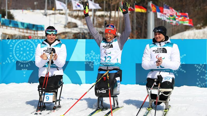 Germany's Andrea Eskau celebrates victory in the women's biathlon 10km sitting at PyeongChang 2018 with silver medallist Neutral Paralympic Athlete Marta Zainullina on the left and bronze medallist Neutral Paralympic Athlete Irina Gulaeva on the right.