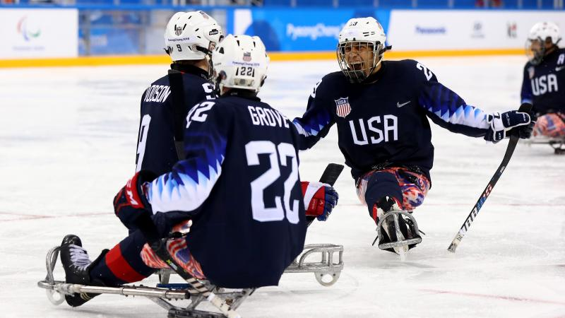 Para ice hockey players celebrate on the ice