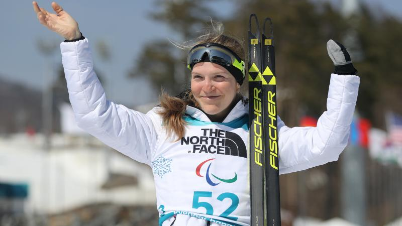 a female Para biathlete celebrates on the podium
