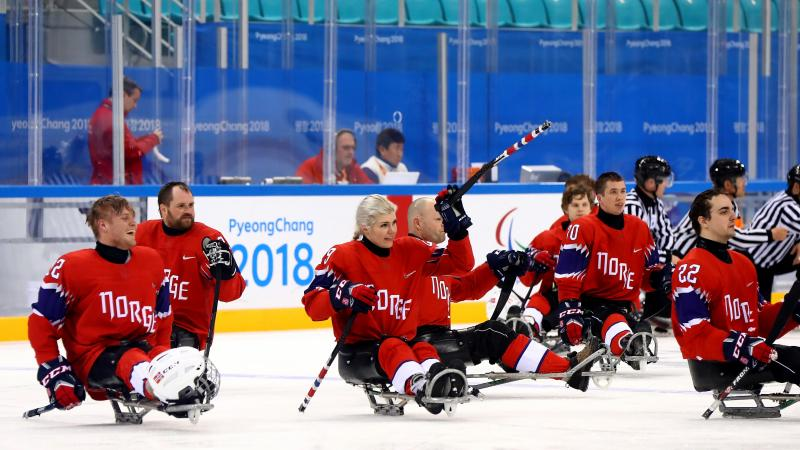 a group of Para ice hockey players celebrating the ice hockey