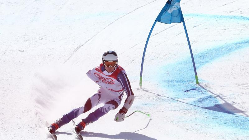 a male Para alpine skier rounds a gate