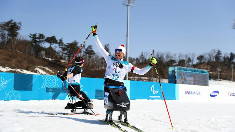 a female Nordic sit skier celebrates on the finish line