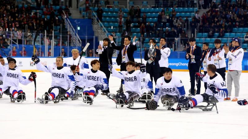 a group of Para ice hockey players on the ice