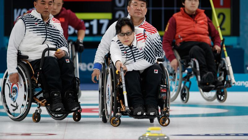 Woman in wheelchair playing curling with three people in wheelchairs observing