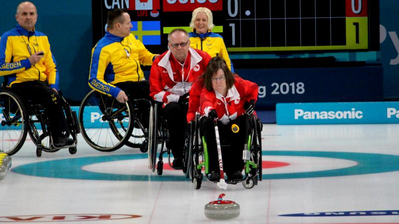 a female wheelchair curler plays a stone