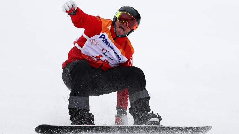 a male Para snowboarder sticks out his tongue at the end of his run
