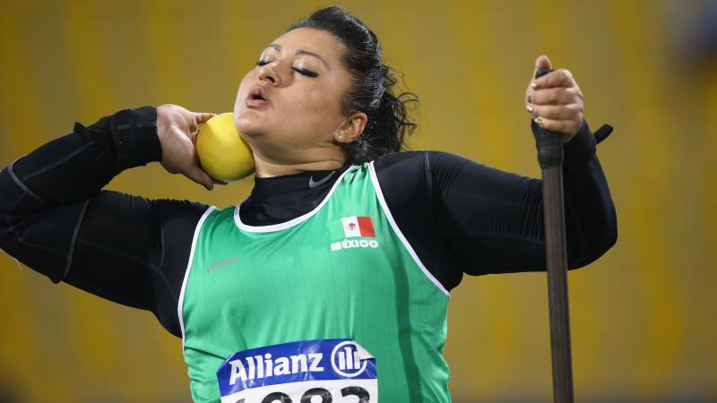 a female shot putter prepares to throw