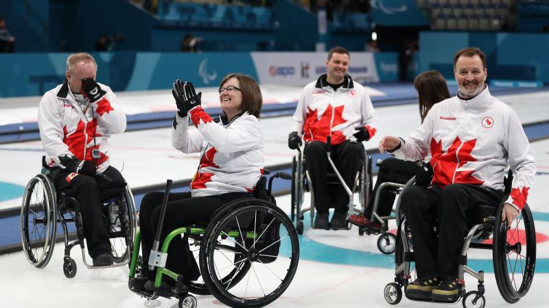 a wheelchair curling team celebrates on the ice