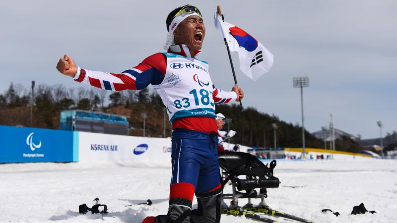 a sit skier celebrates on his knees holding the South Korean flag